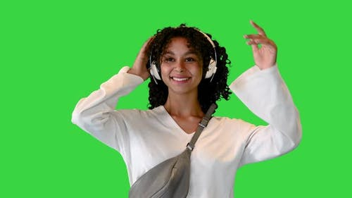 Smiling Young African American Woman Walking and Listening To Music on Headphones on a Green Screen