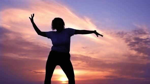 Lady with Short Hair Dances Against Purple Sky at Sunset
