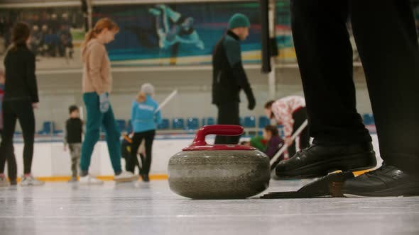 Cover Image for Curling Training - a Woman Pushes the Granite Stone Using a Brush