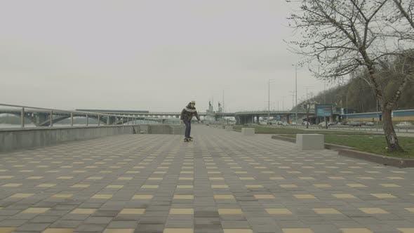 Thumbnail for Teenage Boy Riding Skateboard Down Sidewalk in City