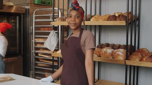 Portrait of Cheerful Afro-American Woman at Work in Bakery