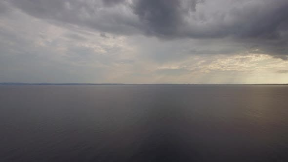 Aerial view of quiet sea, grey clouds in evening sky