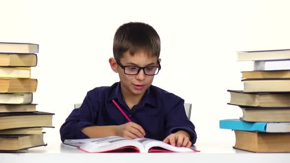 Boy Sits at the Table Leafing Through the Book. White Background