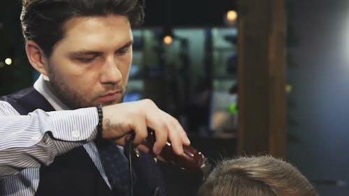 Professionelle Friseur Trimmen Haar von seinem Klienten