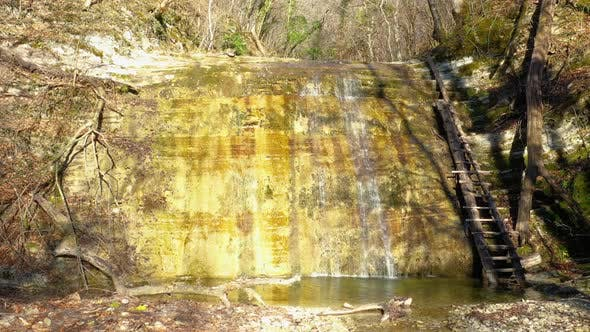 Drone slow flying toward waterfall stream in deep forest
