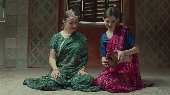 Thumbnail for Rapting Women in Hindu Sari Looking at Jewelry Box