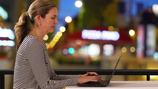 Thumbnail for Attractive Caucasian woman typing on laptop outside at night