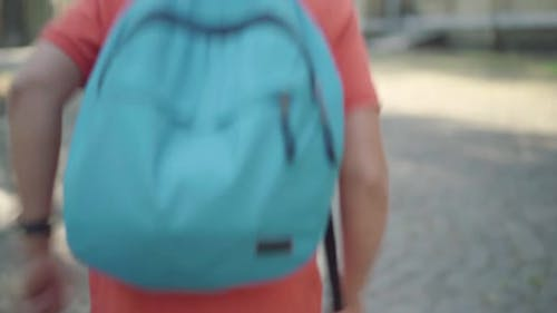 Back View of Schoolboy with Backpack Running Along Sunny Schoolyard Outdoors. Blond Positive