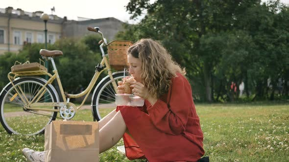 Woman in Red Eats Sandwich From Container on Green Lawn