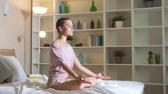 Thumbnail for Young Woman Is Practicing Yoga at Home Relaxing in Simple Body Position Sitting on Bed.