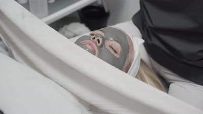 Woman In Grey Face Mask Having Treatment In Salon