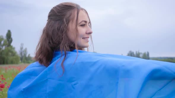 Thumbnail for Portrait of Pretty Girl Standing in a Poppy Field Covered with Flag of Ukraine