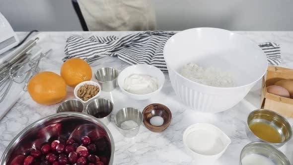 Schritt für Schritt. Zutaten zum Backen von Cranberry-Muffins auf einer Marmor-Küchenoberfläche.