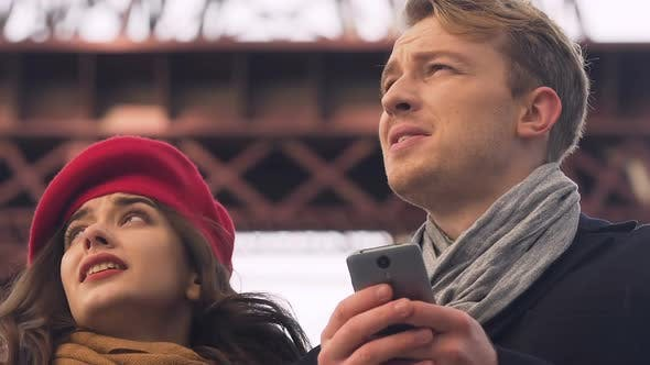 Thumbnail for Young tourist couple looking map in cell phone app, get lost in unknown city