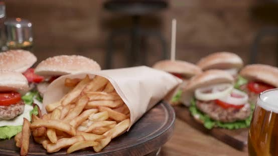 Thumbnail for French Fries and Burgers Rotating on a Wooden Board