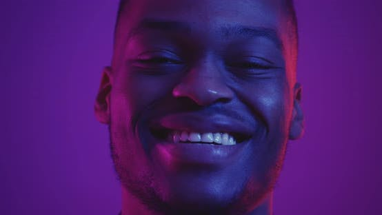 Close Up Portrait Happy African American Guy Laughing Camera Neon Lights Slow Motion
