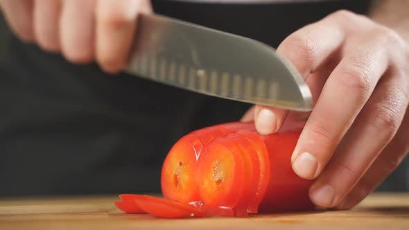 Slicing Sweet Peppers on a Chopping Board By a Chef Closeup of Men's Hands Cutting Red Peppers with