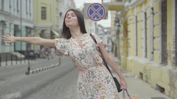 Thumbnail for Carefree Young Woman Wearing Summer Dress with Shopping Bags in Hands Trying To Catch the Taxi