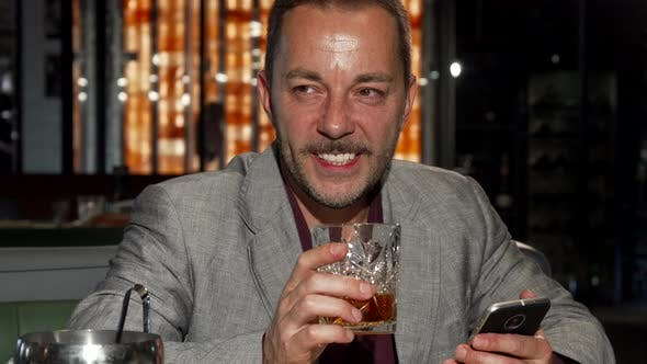 Thumbnail for Handsome Mature Man Using Smart Phone While Tasting Whiskey at the Bar