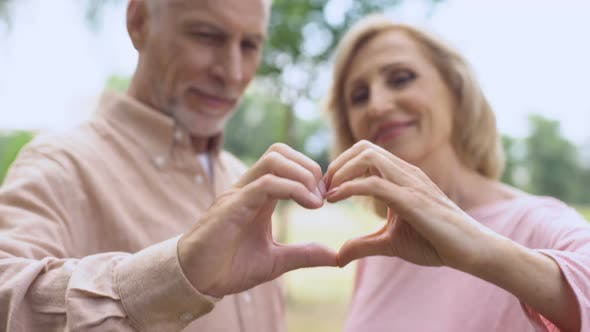 Thumbnail for Positive Aged Couple Showing Heart Sign by Hands and Hugging, Tender Relations