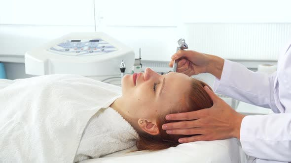 Thumbnail for Cosmetologist Using Some Equipment on Client's Face