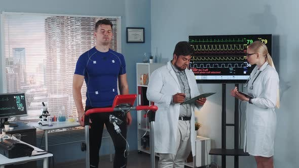 Thumbnail for Two Mixed Race Doctors Discussing EKG Data of Athlete Doing Treadmill Test in Sports Lab