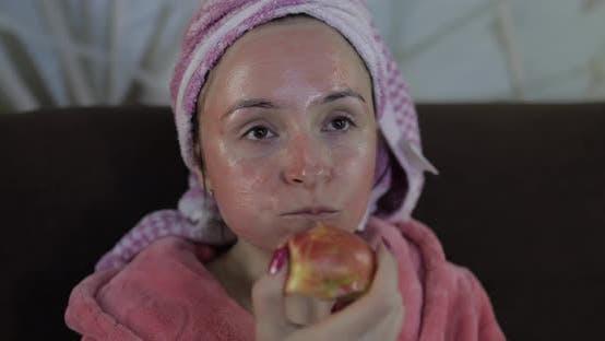 Thumbnail for Woman Watching a Late Night Movie at TV, Eating an Apple. Bathrobe, Facial Mask