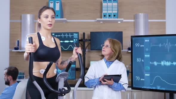 Female Scientist Monitoring the Heart Activity on Female Athlete