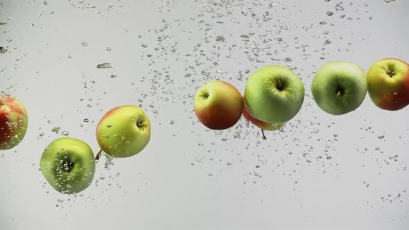 Cover Image for Fresh Colorful Apples Under Water with Splashes and Air Drops on White Background