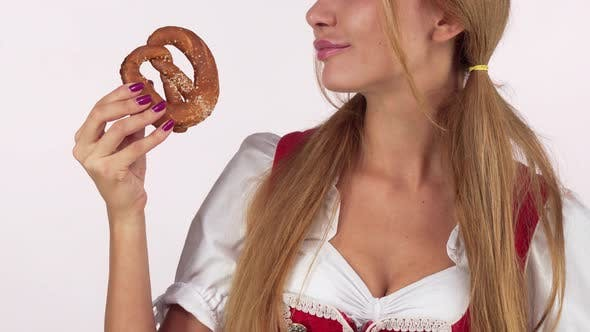 Thumbnail for Unrecognizable Oktoberfest Woman Licking Lips Hungrily, Holding Delicious Pretzel