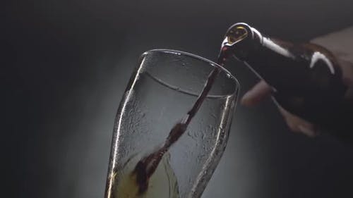 Beer Pouring Into a Glass Against Black Background