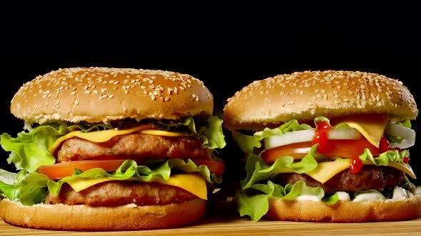 Thumbnail for Close-up of Two Appetizing Burgers with Sesame Buns Rotating on Black Background