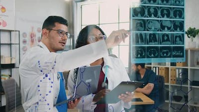 Male and Female Medical Workers Working with X-ray Scan in Medical Office on the Background