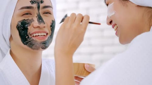 Beautiful young woman in white bathrobe applying a revitalizing black mask onto her friend's face.