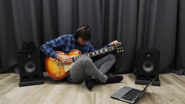 Thumbnail for Man tuning electric guitar before playing and rehearsing for concert in home music recording studio