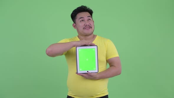 Thumbnail for Happy Young Overweight Asian Man Thinking While Showing Digital Tablet