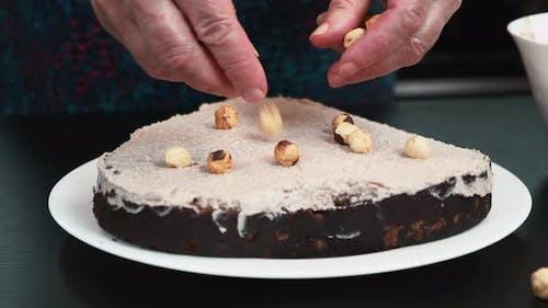 Konditormeister fügt Nüsse auf Biskuitkuchen hinzu. Hausgemachte Bä