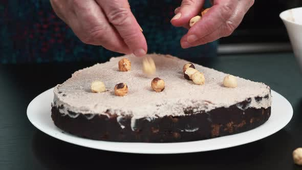Pastry chef is adding nuts on sponge biscuit cake. Homemade bakery
