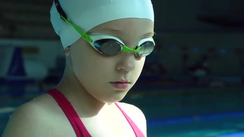 Teenager Girl in Goggles Looking at Camera in Swimming Pool, Close Up.