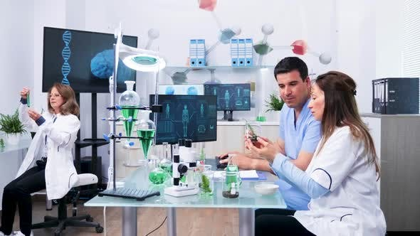 Cover Image for Female Biologist Working Next To Her Assistant