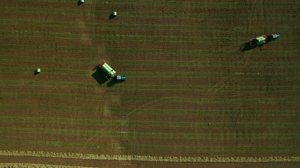 Thumbnail for Modern Agricultural Machinery Works in the Field, Harvesting. Tractor Collects Haystacks in Carts