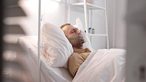 Man Coughing in Hospital Bed