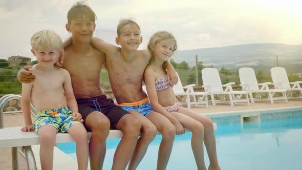 Four Kids Swaying and Having Fun By the Pool Side