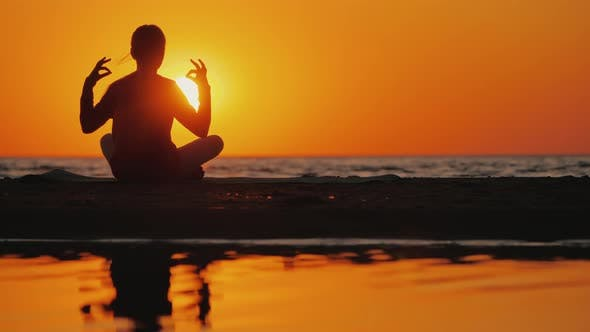 Thumbnail for Young Woman Meditates in a Picturesque Place at Sunset