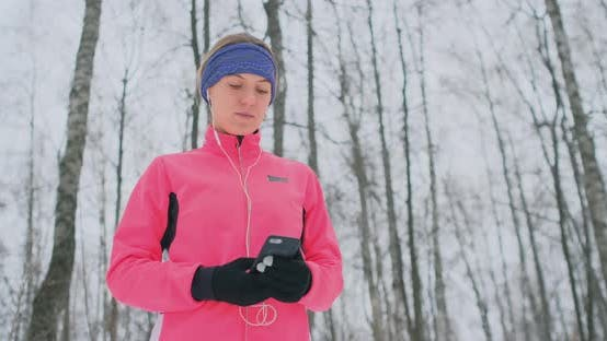 Cover Image for A Young Woman on the Morning Jog Holds in Her Hands a Smartphone Picks a Music Track for Training