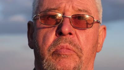 The Wrinkled Face of an Old Man Wearing Sunglasses
