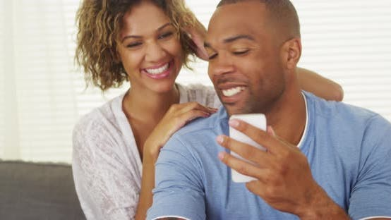 Cover Image for Girlfriend watching over boyfriend's shoulder as he texts