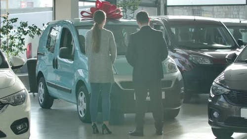 Wide Shot of Man and Woman Standing in Dealership in Front of Aquamarine Car. Back View of Trader