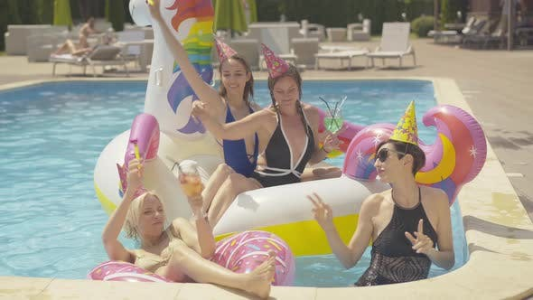 Four Cheerful Young Caucasian Women Dancing in Water Pool on Unicorn and Donut Swimming Rings