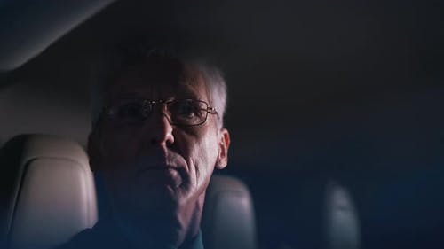 Old Politician Rides in the Back Seat of a Car